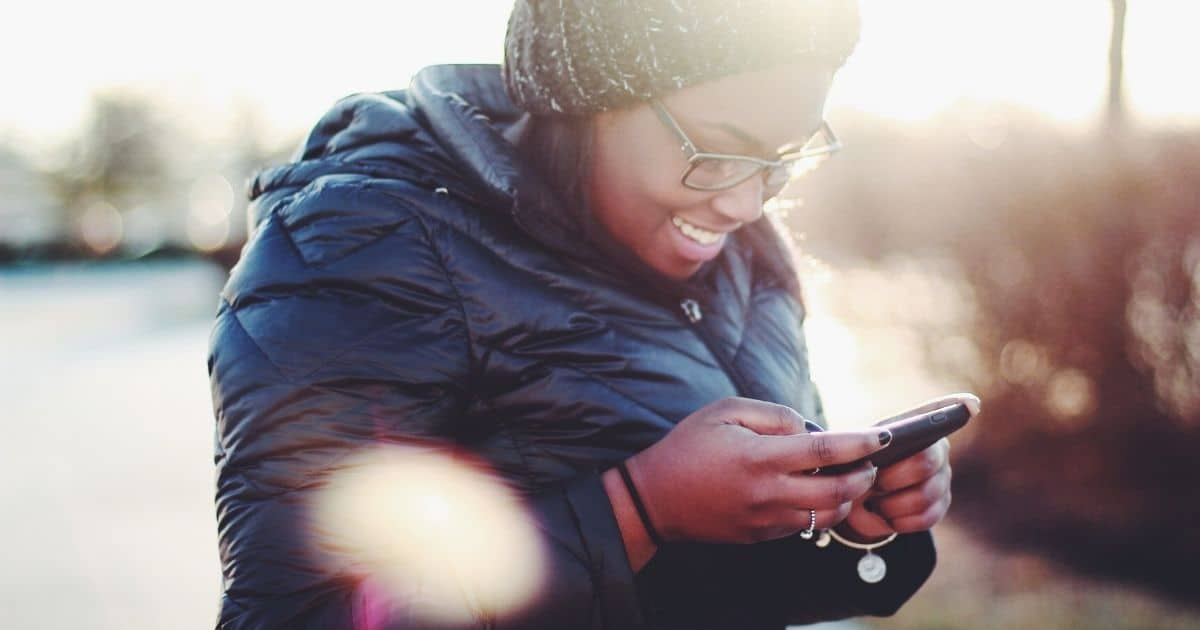 woman texting. learn how to create a sms link for websites